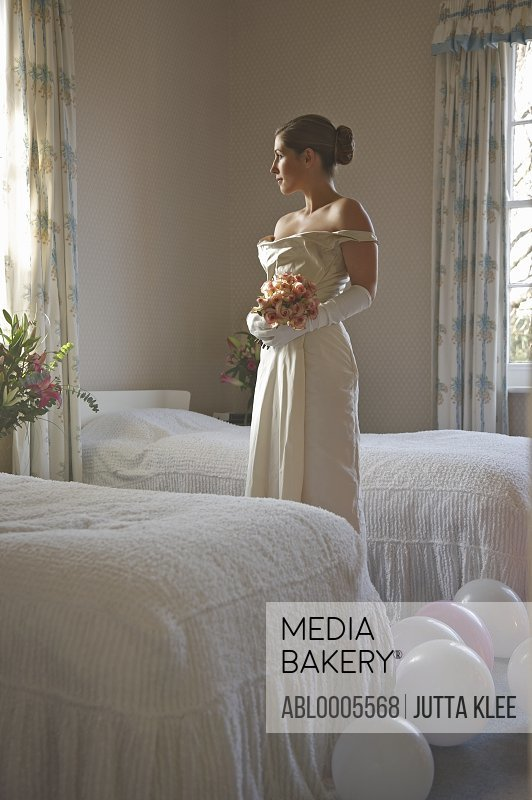 Bride in a white wedding gown holding a bouquet and standing in a bedroom