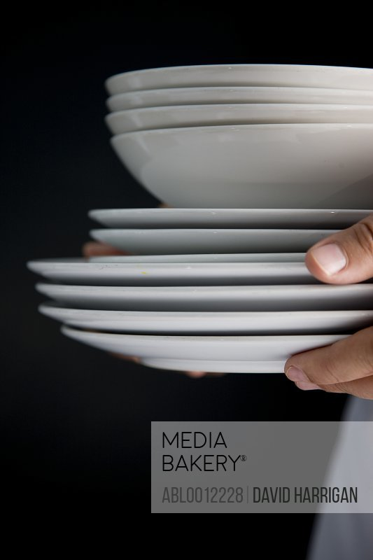 Close up of waiter hands carrying a stack of plates and bowls