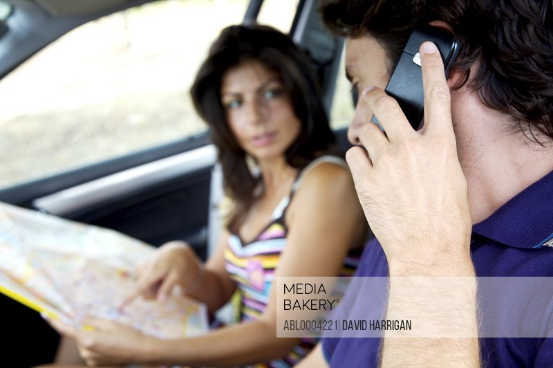 Couple inside a car looking at map