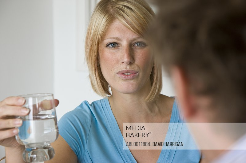 Close up of a young woman talking and holding a glass of water