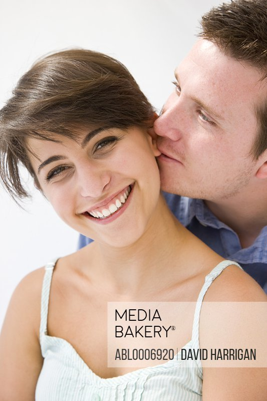 Man Biting Ear Lobe of Smiling Woman