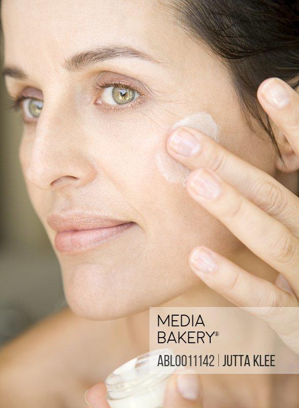 Close up of woman applying moisturizing cream