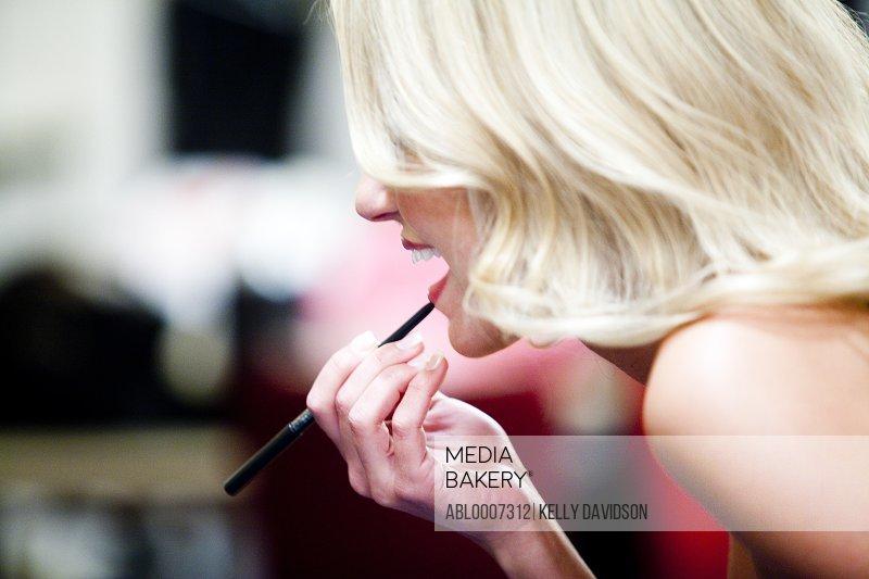 Blonde Woman Applying Lip Liner, Profile