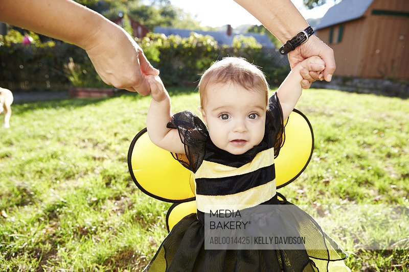 Baby Girl Wearing Bee Costume Taking First Steps in Garden
