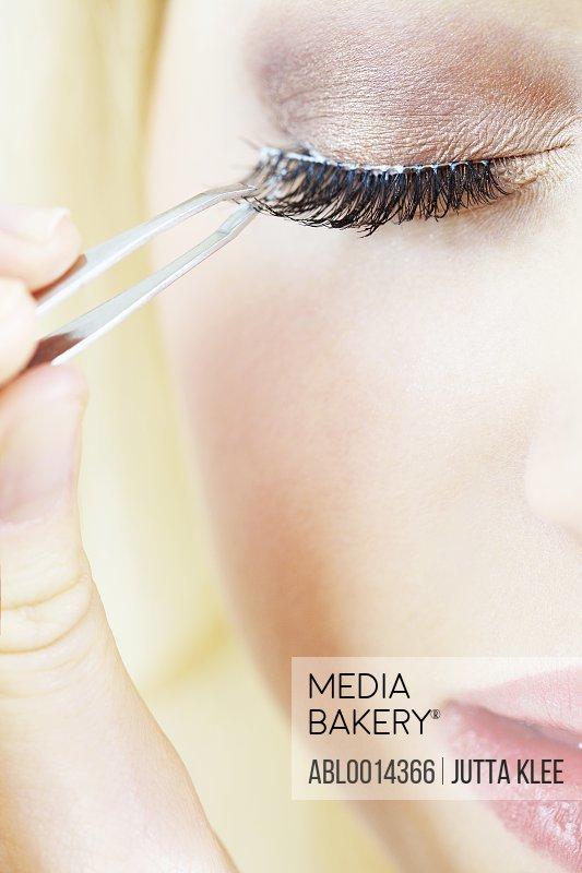 Extreme close up of Woman Applying False Eyelashes