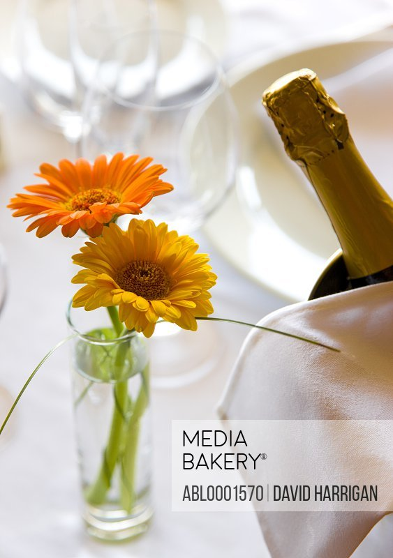 Close up of a vase with flowers and champagne bottle on a restaurant table