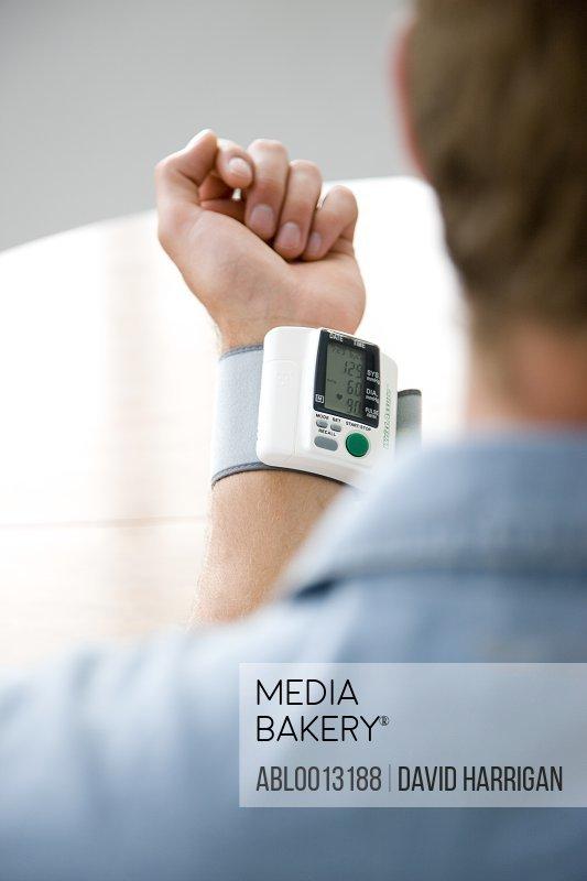 Back View of Man Wearing a Blood Pressure Meter