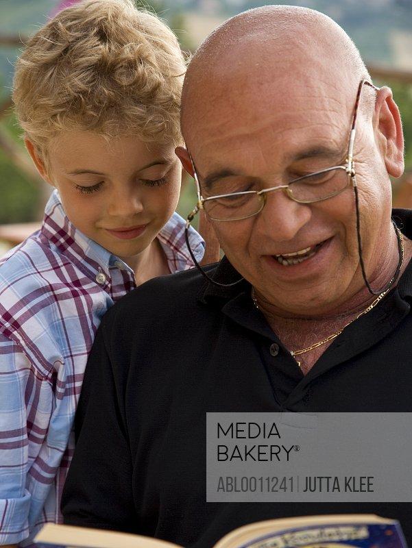 Granddad reading book to grandchild