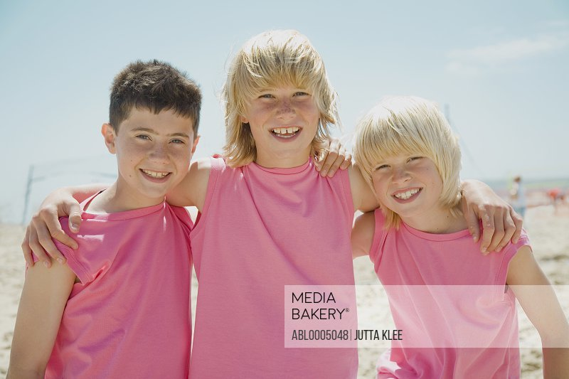 Three smiling boys on a beach wearing identical pink t-shirts