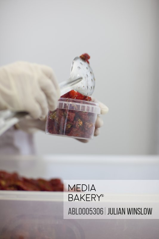 Close up of a worker hand putting sun dried tomatoes in a plastic container with a spoon