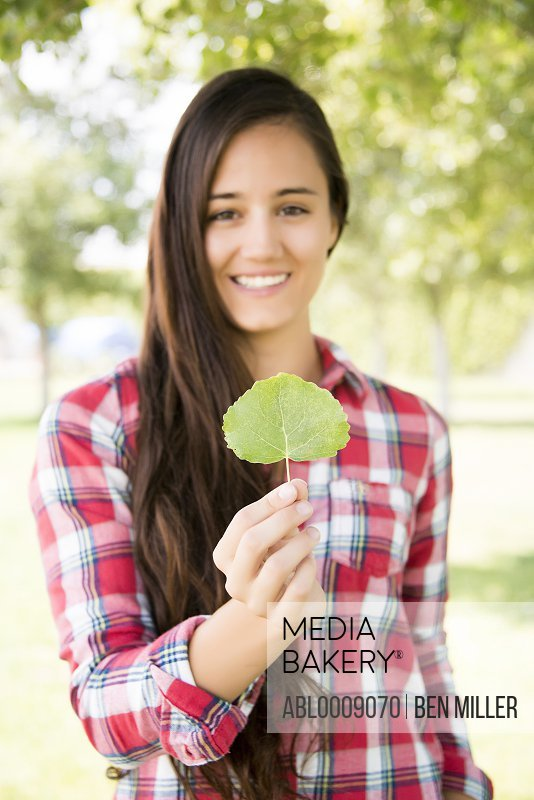 Smiling Woman Holding Leaf
