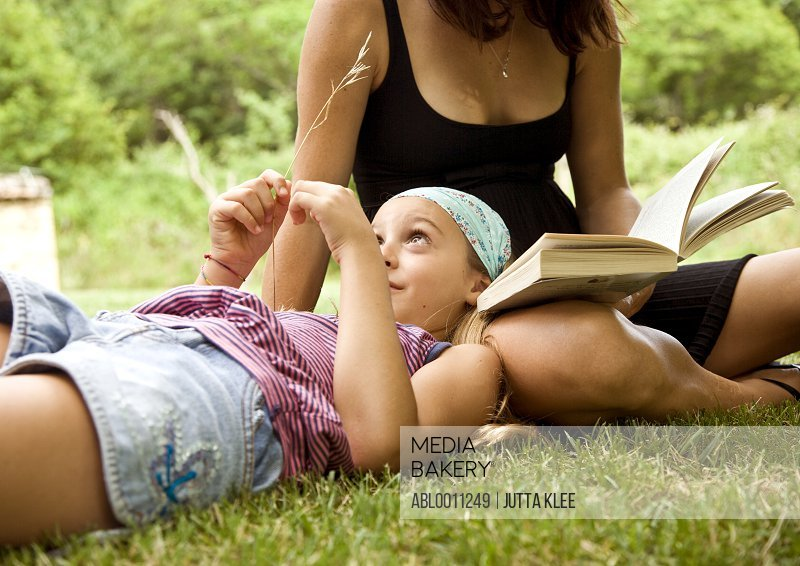 Young girl playing with blade of grass resting head on mother lap