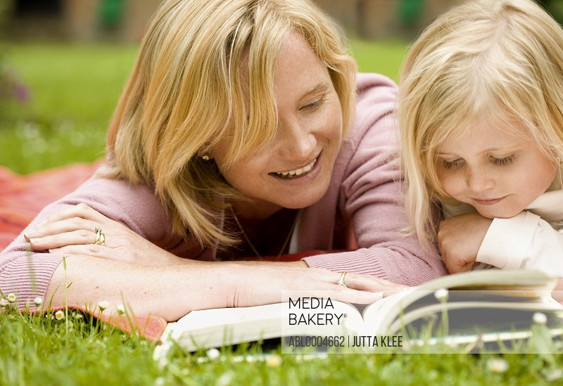 Mother and daughter lying down in the garden reading a book