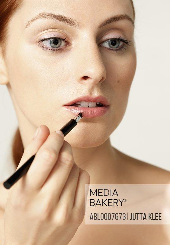 Woman Applying Lipstick with Brush