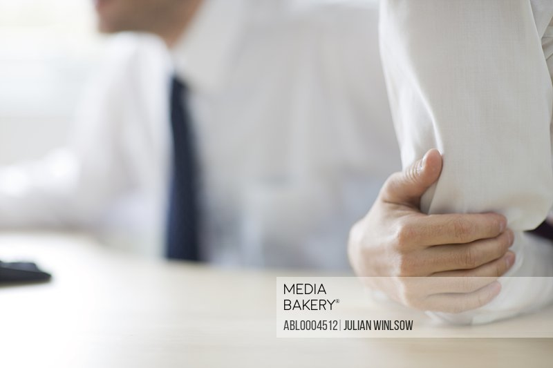 Close up of businessman's arm and hand leaning on desk
