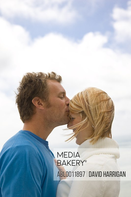 Couple embracing man kissing woman forehead