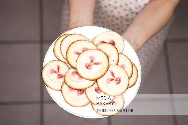 Girl Holding Plate of Cookies with Bunny Faces, Close-up view