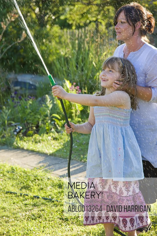 Mother and Daughter Watering Lawn with Garden Hose