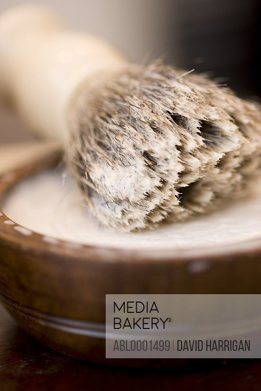 Extreme close up of a shaving brush lying on top of a tub of shaving cream
