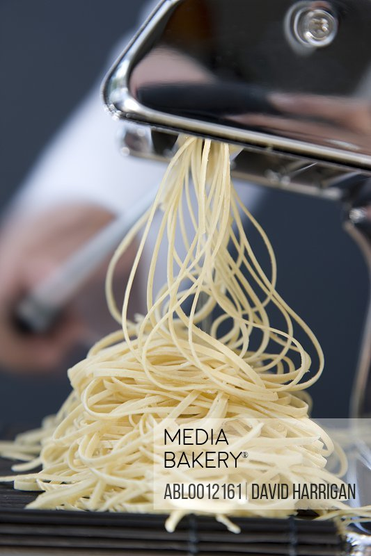 Heap of fresh tagliolini coming out of a pasta maker with hand turning the handle