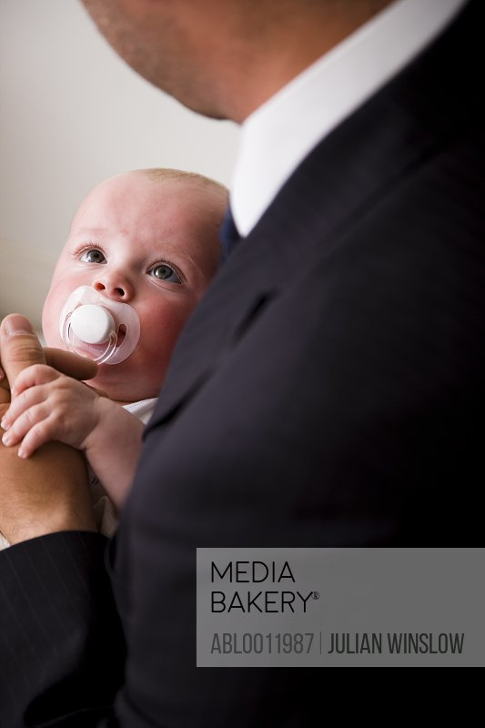 Back view of a businessman holding a baby
