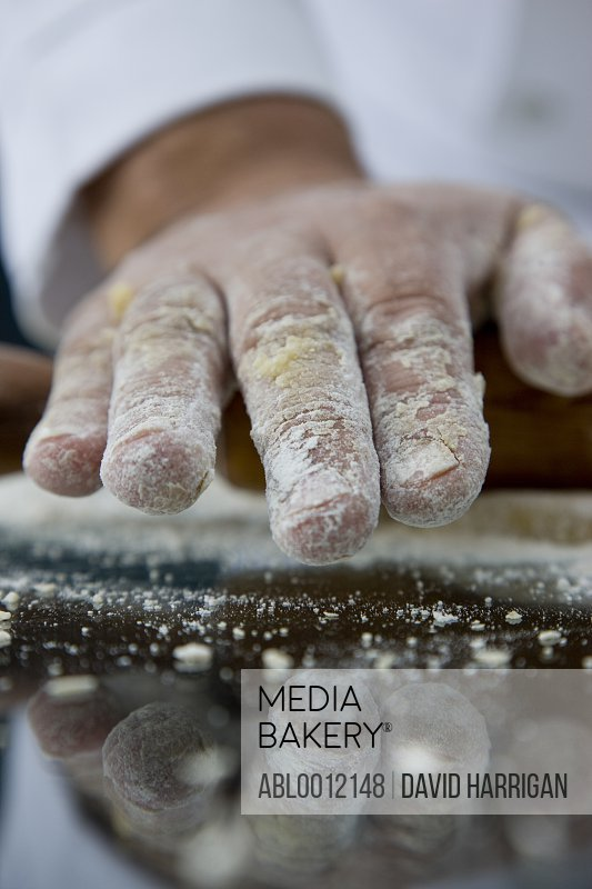 Close up of a chef hand covered in flour rolling a rolling pin across a dough over a glass table