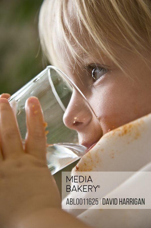 Close up of young blonde boy drinking water
