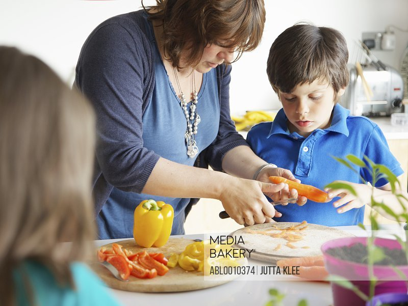 Mother and Son Cutting Vegetables in Kitchen