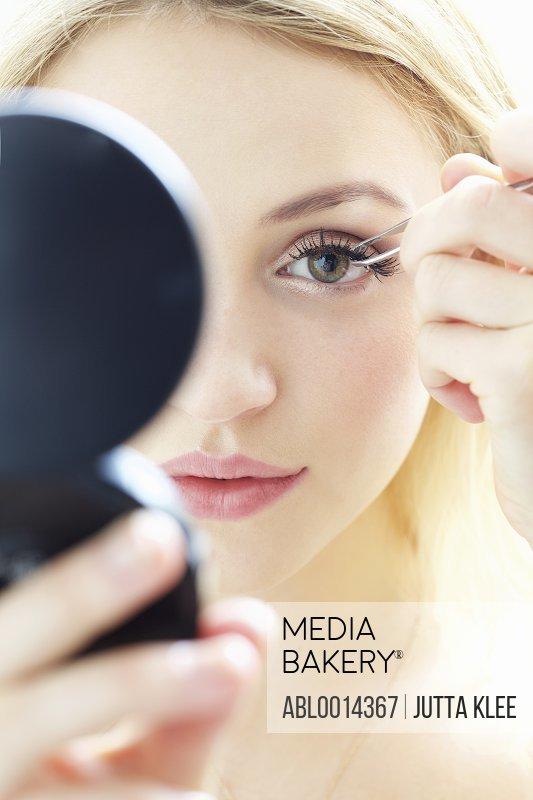 Close up of Young Woman Applying False Eyelashes