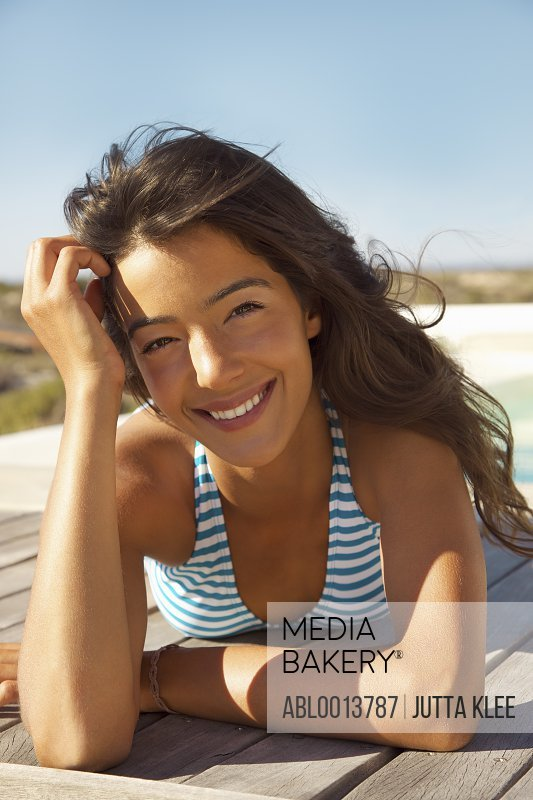 Smiling Young Woman Sunbathing on Deck