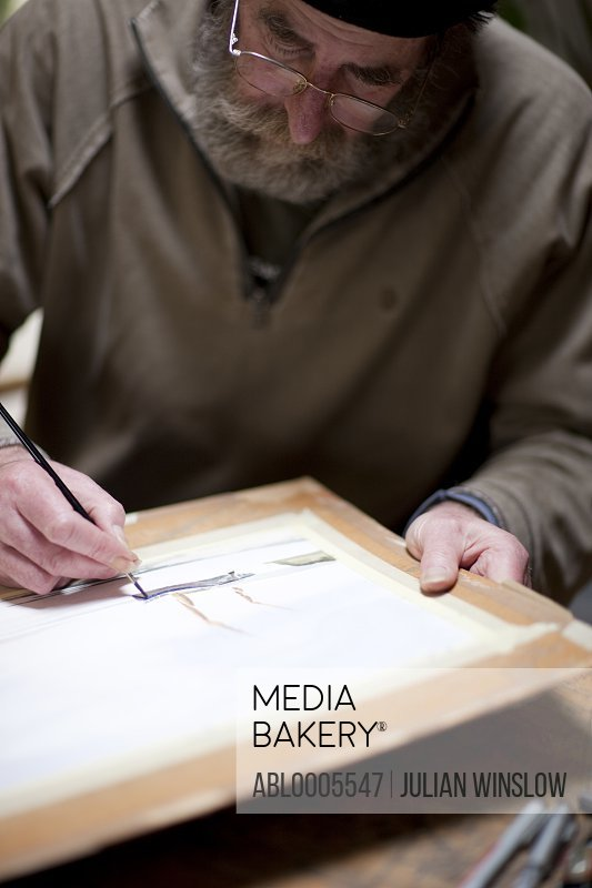 Artist painting at his desk