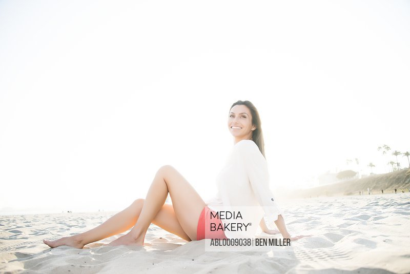 Smiling Woman Sitting on Sand