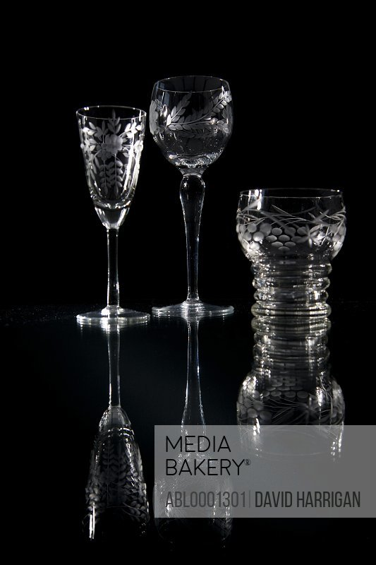 Three empty crystal glasses on a glass surface