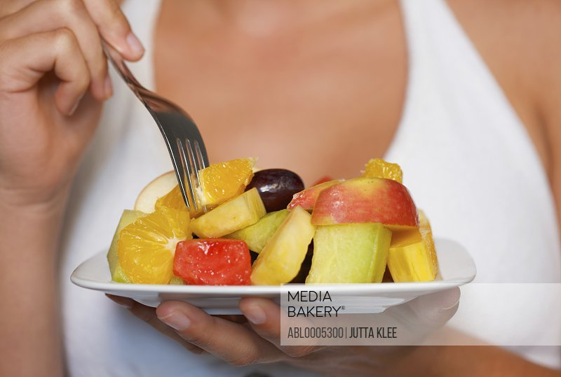 Close up of a young woman holding a bowl of fruit salad