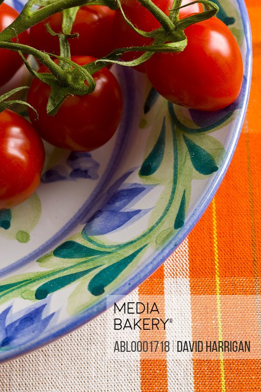 Close up of small plum tomatoes on the vine on a plate