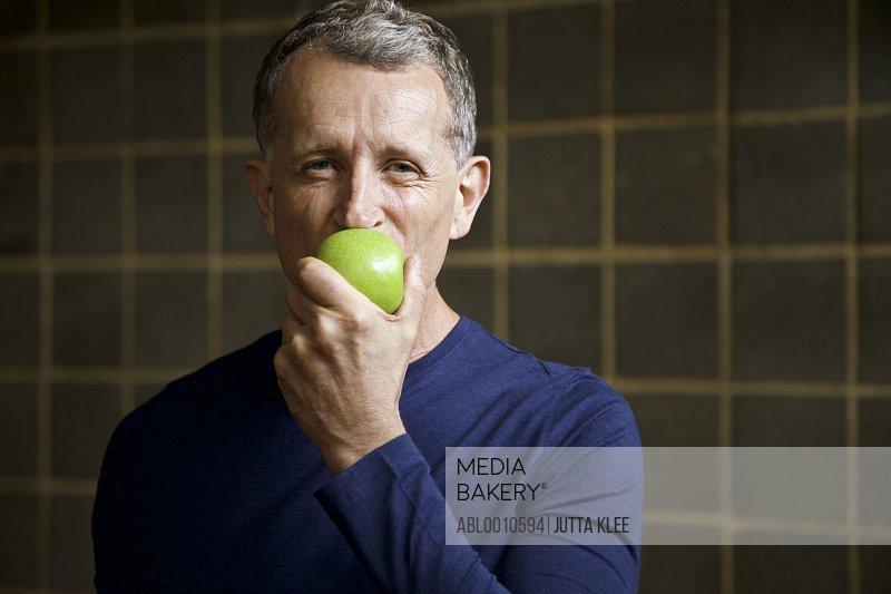 Mature Man Biting an Apple