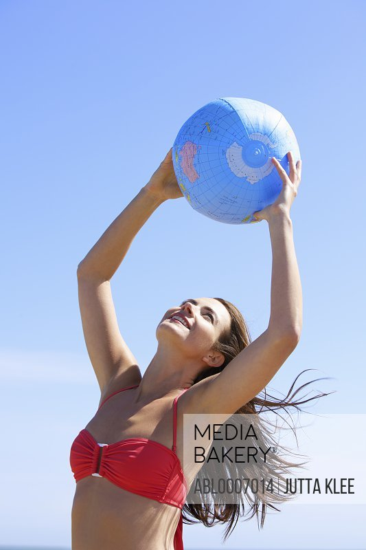 Smiling Woman Holding Inflatable Globe above Head