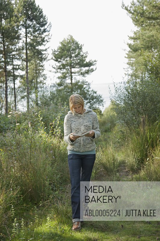 Young woman walking in a forest reading a book