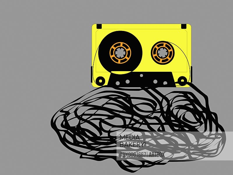 Damaged audio cassette against a gray background