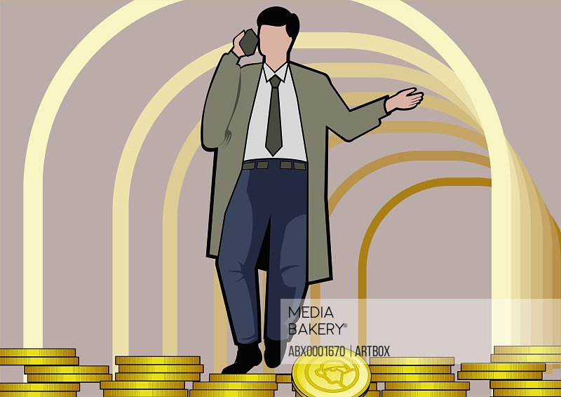 Businessman on gold coins using a mobile phone
