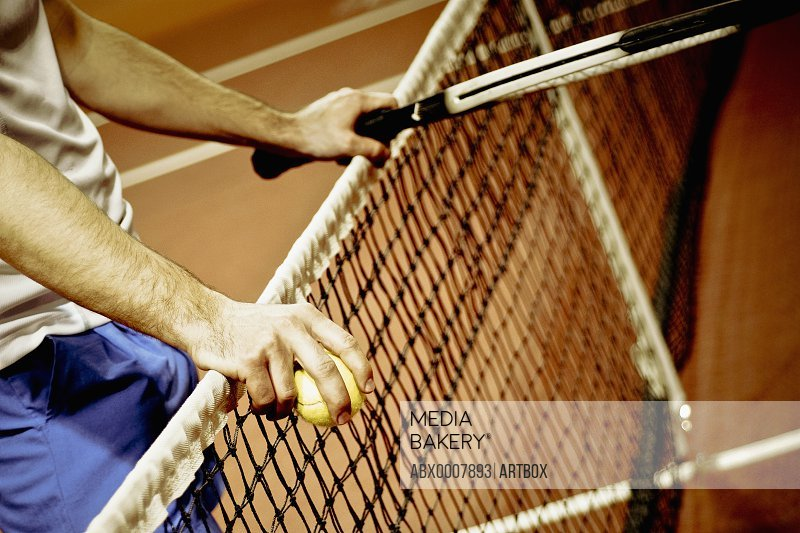 Mid section view of a person holding a tennis racket and tennis balls