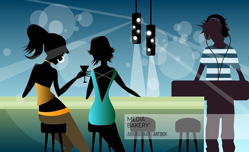 Two women sitting at a bar with a dj playing music