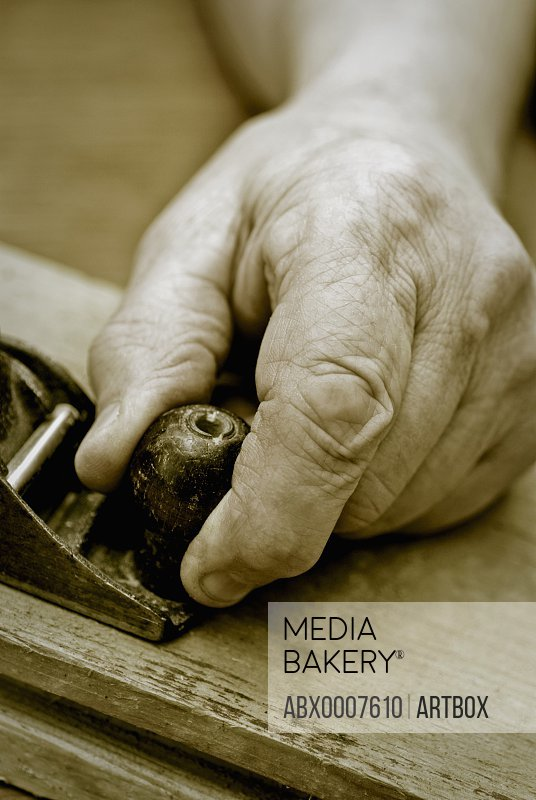 Close-up of a carpenter's hand shaving a wood plank