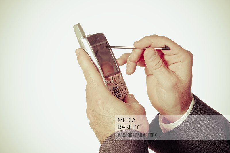 Close-up of a businessman's hand using a personal data assistant