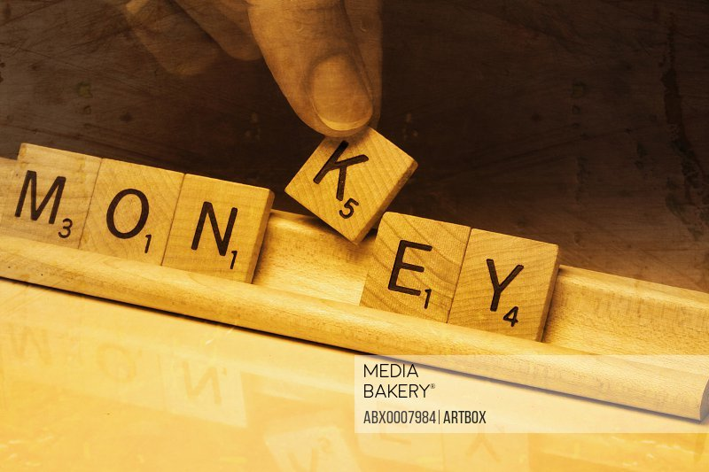 Close-up of a person's hand picking up alphabet K from text Monkey made by wooden blocks