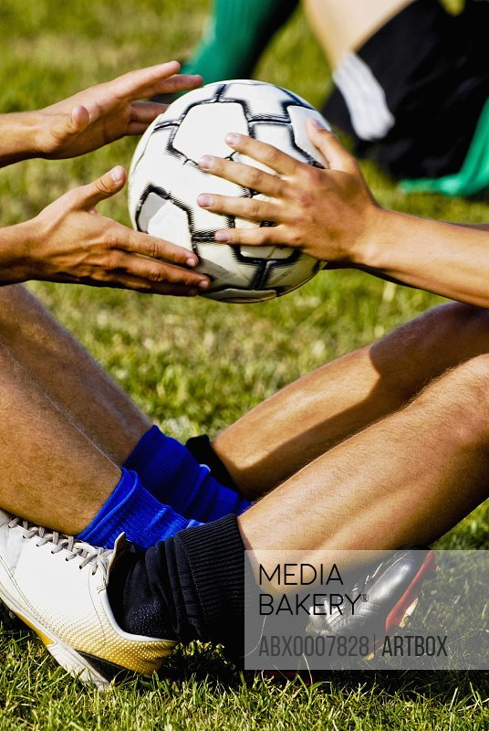 Low section view of two soccer players exercising