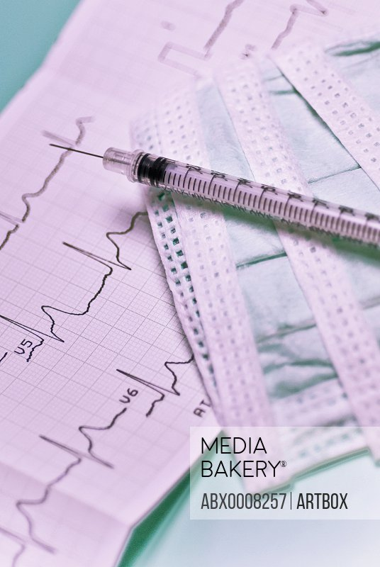Close-up of an electro cardiogram report with a syringe