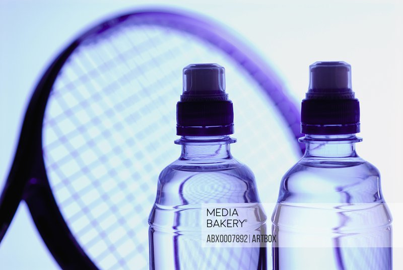 Close-up of two water bottles and a tennis racket