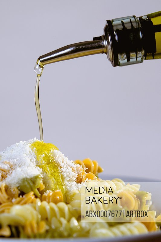 Olive oil being poured on a plate of pasta