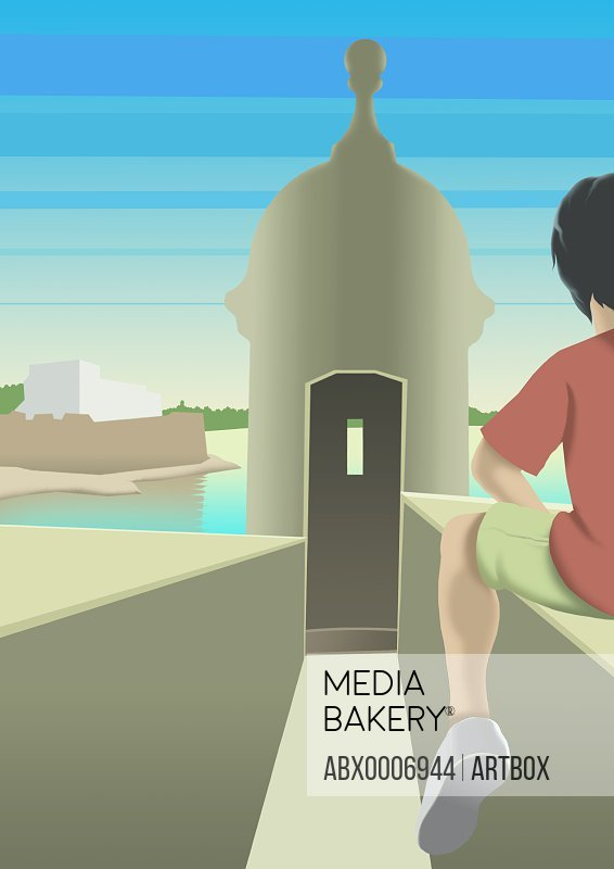 Rear view of a boy sitting on wall in front of a tower